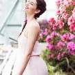 Portrait of a beautiful brunette woman in pink dress and colorful make up outdoors in azalea garden — Stock Photo #49966271