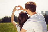 Beautiful couple on a date walking at the park hugging and making heart gesture — Foto Stock