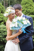 Young couple kissing in wedding gown. Bride holding bouquet with white lilies — Stock Photo