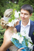 Young couple kissing in wedding gown. Bride holding bouquet with white lilies — Photo