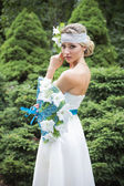 Blonde woman in wedding dress holding bouquet with white lilies — Photo