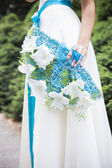 Blonde woman in wedding dress holding bouquet with white lilies — Stock Photo