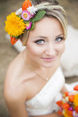 Beautiful bride in white wedding dress holding flower bouquet and smiling — Photo