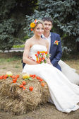 Young couple kissing in wedding gown. Bride holding bouquet of flowers — 图库照片