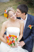 Young couple kissing in wedding gown. Bride holding bouquet of flowers — Photo