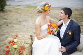 Jong koppel zoenen in trouwjurk. bruid bedrijf boeket van bloemen — Stockfoto