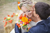 Young couple kissing in wedding gown. Bride holding bouquet of flowers — Stockfoto