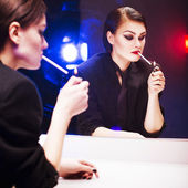 Beautiful brunette woman in business costume lighting a cigarette in front of the mirror with color backlight — Stock Photo