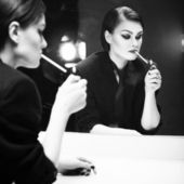 Beautiful brunette woman in business costume lighting a cigarette in front of the mirror with color backlight. Black and White — Stockfoto