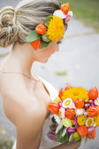 Beautiful bride in white wedding dress holding flower bouquet and smiling — Stock Photo
