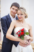 Young couple kissing in wedding gown. Bride holding bouquet with red roses — Stock Photo