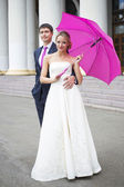 Young couple hugs in wedding gown with pink umbrella — Stock Photo