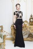 Linda mulher loira real em pé perto de mesa retrô em vestido de luxo, olhando em frente de si mesma. indoor — Foto Stock