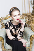 Beautiful blonde royal woman sitting on a retro chair in gorgeous luxury dress, looking at camera. Indoor — Stock Photo