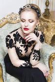 Loira real mulher bonita sentada numa cadeira retrô no vestido de luxo, olhando para a câmera. indoor — Fotografia Stock