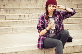 Brunette woman in hipster outfit sitting on steps on the street. Toned image. Copy Space — Stock Photo