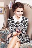 Mooie brunette rijke saucy vrouw in elegante jurk zittend op een stoel in een kamer met klassieke interieur drinken van wijn. binnen — Stockfoto