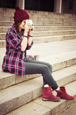 Brunette woman in hipster outfit sitting on steps on the street, photographing. Toned image — Stock Photo