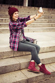 Brunette woman in hipster outfit sitting on steps and taking selfie on retro camera on the street. Toned image — Stock Photo