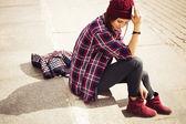 Brünette frau in hipster-outfit auf schritte auf der straße sitzen. getönten bild. textfreiraum — Stockfoto