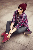 Brunette woman in hipster outfit sitting on a scateboard on the street. Toned image. — Stock Photo