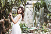 Beautiful brunette woman in white dress and sensual pose in cactus garden. Copy space — Stock Photo