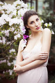 Portrait of a beautiful brunette woman in pink dress and colorful make up outdoors in azalea garden — Stock Photo