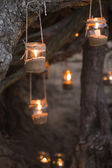 Beautiful decorated romantic place for a date with jars full of candles hunging on tree at night — Stock Photo