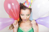 Brunette Woman in a Birthday Cap Holding Balloons and Smile Happily — Stock Photo