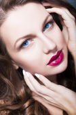 Beautiful brunette woman with creative make up violet eye shadows full red lips, blue eyes and curly hair with her hand on her face — Стоковое фото