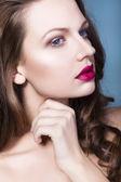 Hermosa mujer morena con creativos de violeta rojo lleno de sombras de ojos labios, maquillaje azul ojos y pelo rizado con su mano en la cara — Foto de Stock