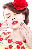 Brunette woman in yellow and red dress with poppy flower in her hair, poppy ring and creative nails, closed eyes on white background — Stock Photo