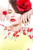 Bruna donna in abito giallo e rosso con papavero fiore tra i capelli, anello di papavero e creativi chiodi, chiuse gli occhi su sfondo bianco — Foto Stock