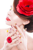 Brunette woman with poppy flower in her hair, poppy ring and creative nails on white background — Stockfoto