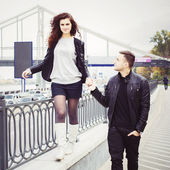 Couple walking holding hands outdoors. He supports her while she walks on parapet — Stock Photo