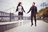 Couple in leather jackets jumping on seafront on a cloudy day outdoors — Stock Photo