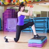 Donna facendo esercizi con manubri su una tavola di passaggio in una palestra in forma — Foto Stock
