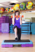 Fit Woman doing exercises with Dumbbells on a Step Board in a Gym — Stock Photo