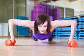 Fit Woman doing push-ups with Dumbbells on a floor in a Gym smiling — Stock Photo