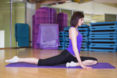 Fit Woman doing yoga exercise on a Mat in a Gym smiling — Stock Photo