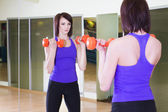 Fit Woman standing with Dumbbells in a Gym looking on herself into a Mirror — Stock Photo