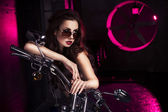 Brunette sexy woman in black underwear, heels and sunglasses in studio in red light on a motorcycle. Indoors. Copy Space — Stock Photo