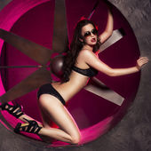Brunette sexy woman in black underwear, heels and sunglasses in studio in red light in the hole in a wall. Indoors — ストック写真