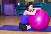 Fit Woman doing exercises with a ball on a Mat in a Gym smiling — ストック写真