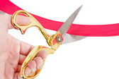 Businessman cutting a red ribbon with a pair of scissors — Stock Photo