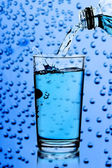 Pouring water into glass on blue background — 图库照片