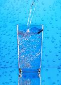 Derramando água em vidro em fundo azul. — Foto Stock