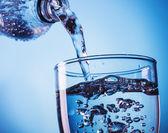 Versando acqua da bottiglia in vetro — Foto Stock