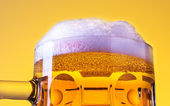 Mug fresh beer with cap of foam isolated over yellow background — Stock Photo
