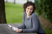 Pretty woman reading at the park — Stock Photo